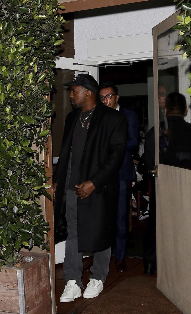 SPOTTED: Kanye West In Adidas Yeezy Season Shirt And Sneakers, Public Enemy Hat And Longline Coat
